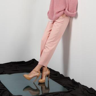 Vrouwelijke benen in broek die aan de muur leunt