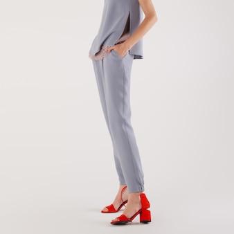 Vrouwelijke benen in broeken en rode schoenen