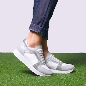 Vrouwelijke benen in comfort casual urban sneakers staan op zijn tenen in profiel