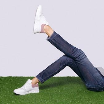 Vrouwelijke benen in comfort casual urban sneakers tot op het gras.
