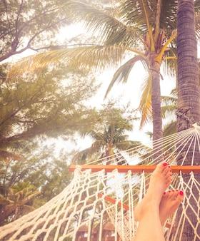 Vrouwelijke benen in een hangmat op een achtergrond van de zee, palmbomen en zonsondergang