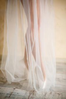 Vrouwelijke benen in een jurk van lichte stof en spitzen