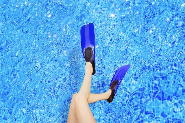 Vrouwelijke benen in flippers bij het zwembad