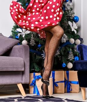 Vrouwelijke benen in gestippelde panty dichtbij kerstboom