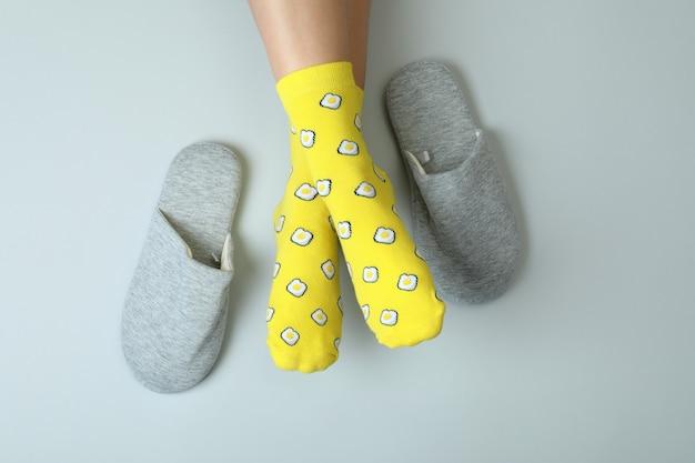 Vrouwelijke benen in grappige sokken op grijs met pantoffels