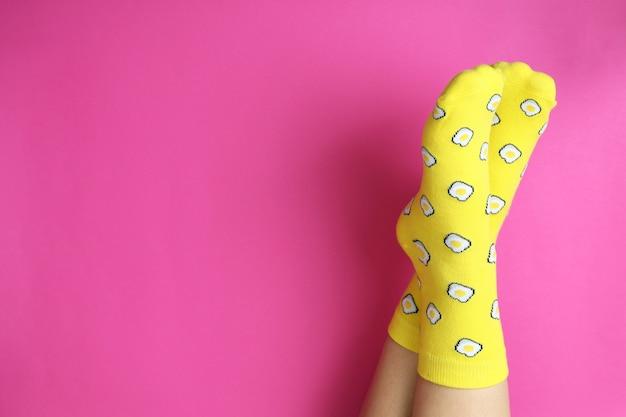 Vrouwelijke benen in grappige sokken op roze