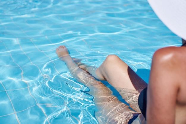 Vrouwelijke benen in het water zwembad. zomervakantie