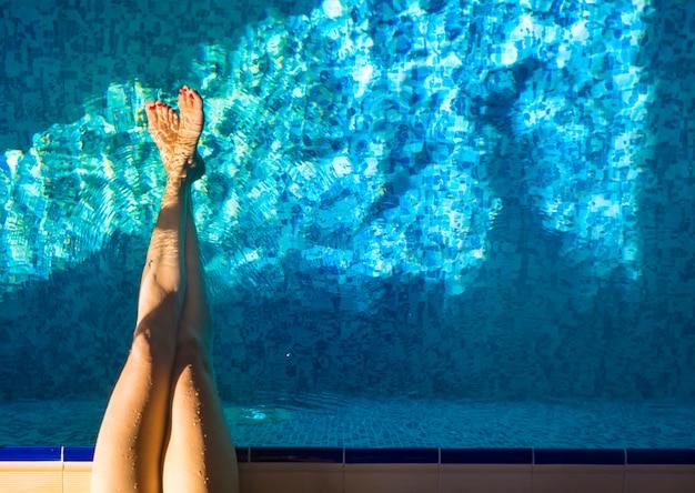 Vrouwelijke benen in het zwembad water. activiteit en gezond leven concept. actieve rust en vakanties.