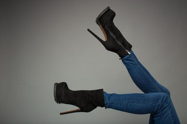 Vrouwelijke benen in hoge laarzen, geïsoleerd op een grijze achtergrond