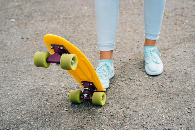 Vrouwelijke benen in jeans en tennisschoenen die zich dichtbij helder geel skateboard bevinden