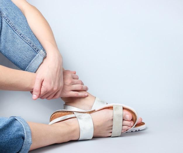 Vrouwelijke benen in jeans en trendy sandalen die op wit zitten.