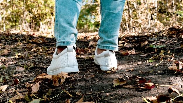 Vrouwelijke benen in jeans en witte sneakers. detailopname