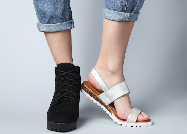 Vrouwelijke benen in jeans geschoeid in laars en sandaal op wit.