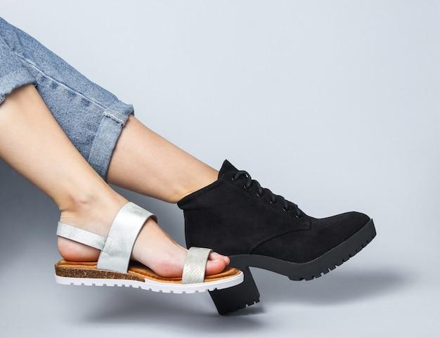 Vrouwelijke benen in jeans geschoeid in laars en sandaalzitting op wit.