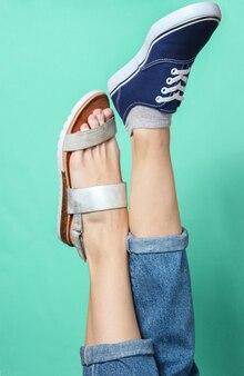 Vrouwelijke benen in jeans geschoeid in sandaal en sneaker op blauw. seizoensgebonden schoenen. creatieve mode-opname