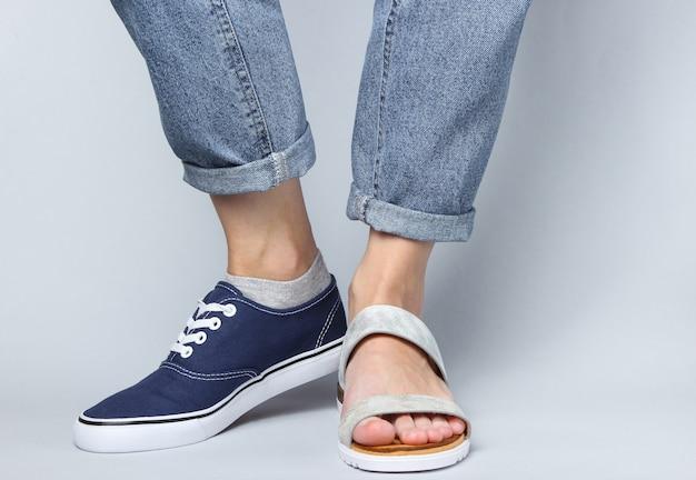 Vrouwelijke benen in jeans geschoeid in tennisschoen en sandaal op wit.