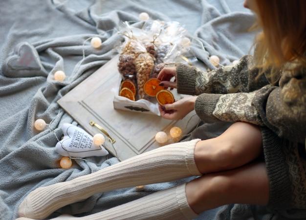 Vrouwelijke benen in kerstsokken gekleed in een warm sweathermeisje dat een zoete snack in haar handen houdt