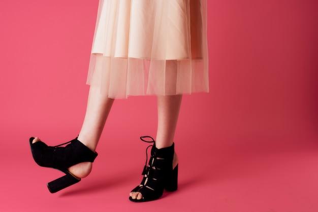 Vrouwelijke benen in kleding modieuze schoenen luxe roze achtergrond