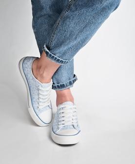 Vrouwelijke benen in korte jeans en sneakers staan op een wit