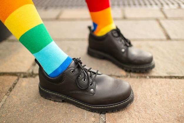 Vrouwelijke benen in lgbt regenboogsokken die mannelijke laarzen dragen.