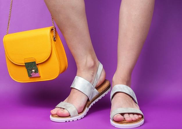 Vrouwelijke benen in modieuze leren sandalen en gele tas op paars. zomerschoenen.