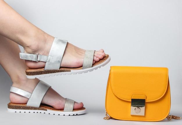 Vrouwelijke benen in modieuze leren sandalen en gele tas op wit. zomerschoenen.