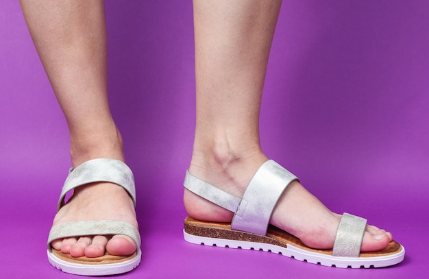 Vrouwelijke benen in modieuze leren sandalen op paars. zomerschoenen.