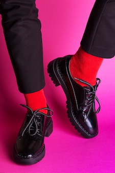 Vrouwelijke benen in rode sokken en stijlvolle zwarte schoenen op een roze achtergrond. modetrends. mooie vrouwelijke schoenen
