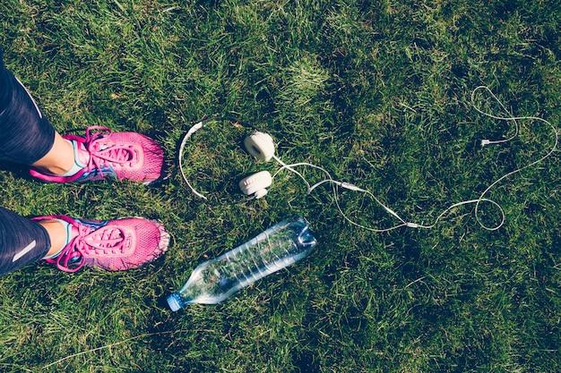 Vrouwelijke benen in roze sneakers, witte koptelefoon en een plastic fles water op het gras
