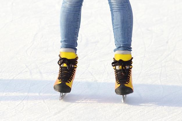 Vrouwelijke benen in schaatsen op een ijsbaan. sporten en amusement. rust- en wintervakanties.