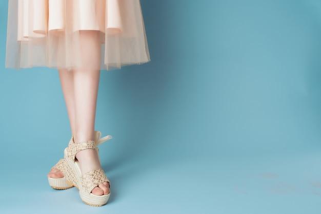 Vrouwelijke benen in schoenen jurk bijgesneden weergave close-up blauwe achtergrond mode