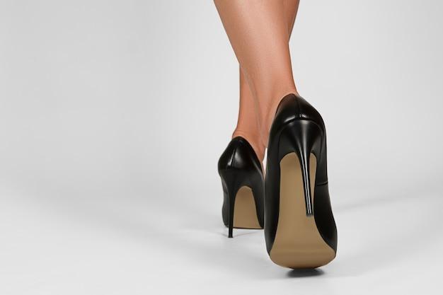 Vrouwelijke benen in schoenen met hoge hakken