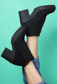 Vrouwelijke benen in spijkerbroek en trendy laarzen op blauw. stijlvolle winterschoenen voor dames. minimalistisch mode-shot