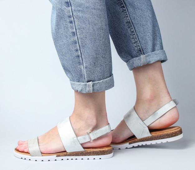 Vrouwelijke benen in spijkerbroek en trendy lederen sandalen lopen op wit. stijlvolle zomerschoenen voor dames.