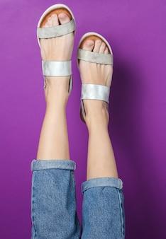 Vrouwelijke benen in spijkerbroek en trendy leren sandalen op paars. stijlvolle zomerschoenen voor dames. minimalistisch mode-shot