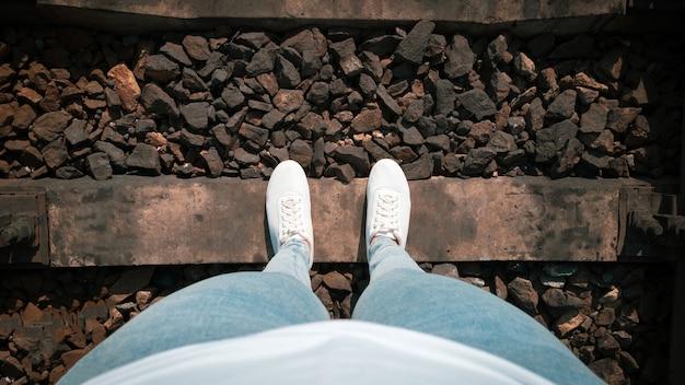 Vrouwelijke benen in spijkerbroek en witte sneakers op spoorlijnen vanaf de eerste persoon