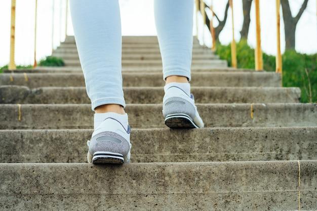 Vrouwelijke benen in spijkerbroeken en sneakers, beklim de concrete treden in openlucht