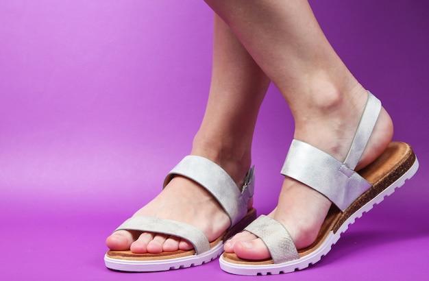 Vrouwelijke benen in trendy leren sandalen op paars. zomerschoenen.