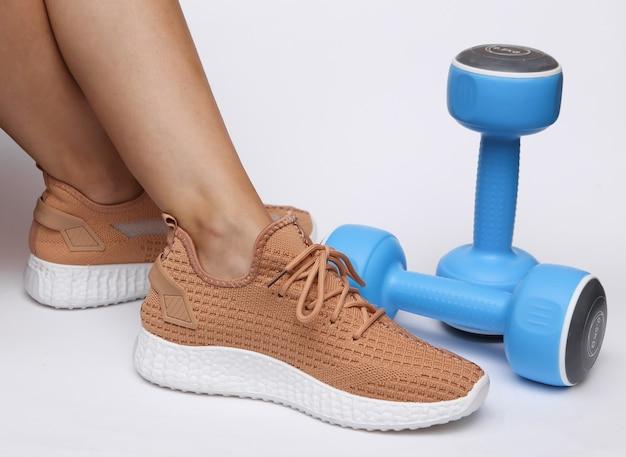 Vrouwelijke benen in trendy sportschoenen en halters op een witte achtergrond. sportconcept