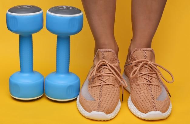 Vrouwelijke benen in trendy sportschoenen en halters op gele achtergrond. sportconcept