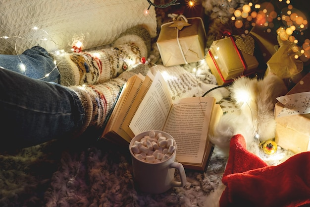 Vrouwelijke benen in warme gebreide sokken op een plaid naast de kerstboom en versieringen, een boek en een kop warme chocolademelk. sfeer van vakantie en comfort
