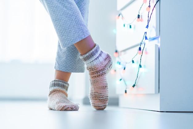 Vrouwelijke benen in warme gebreide zachte, gezellige sokken in de winter thuis.