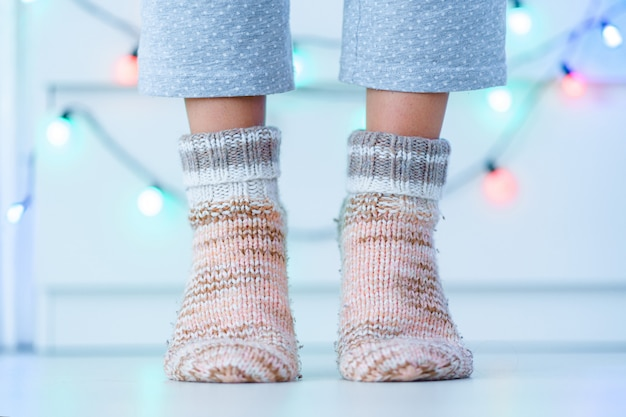 Vrouwelijke benen in warme gebreide zachte gezellige sokken in de winter thuis.