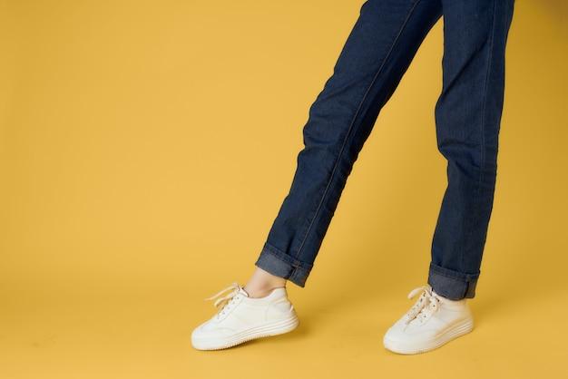 Vrouwelijke benen in witte sneakers poseren gele straatstijl als achtergrond