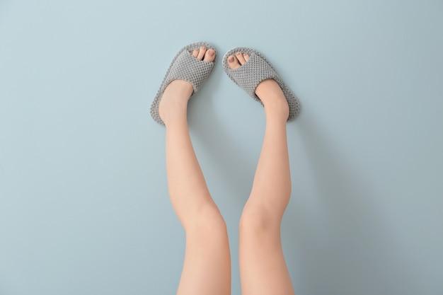 Vrouwelijke benen in zachte pantoffels op kleur