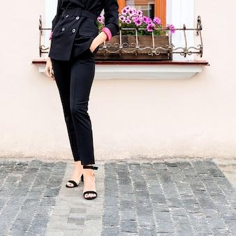 Vrouwelijke benen in zwart pantsuit