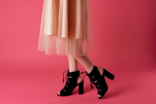 Vrouwelijke benen in zwarte schoenen poseren bijgesneden weergaven roze achtergrond mode