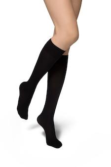 Vrouwelijke benen in zwarte sokken op witte achtergrond
