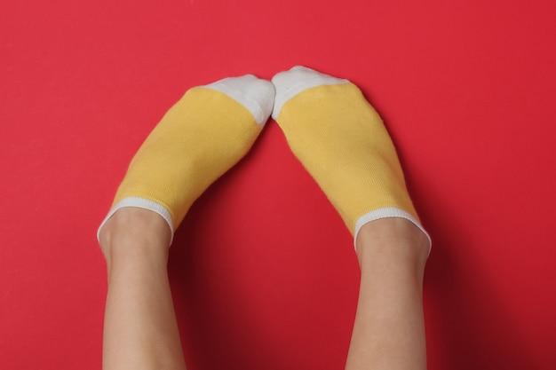 Vrouwelijke benen met gele sokken op rode studioachtergrond