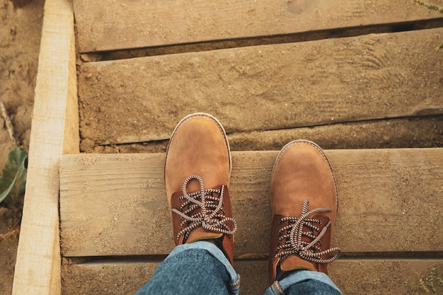 Vrouwelijke benen met laarzen op houten treden met zand